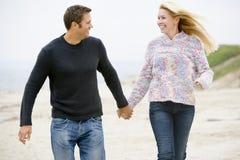 Coppie che camminano alle mani della holding della spiaggia fotografia stock libera da diritti