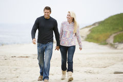 Coppie che camminano alle mani della holding della spiaggia Fotografia Stock