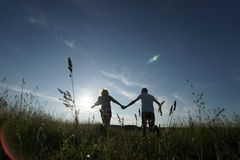 Coppie che camminano attraverso il campo Fotografia Stock Libera da Diritti