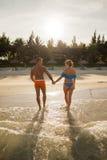 Coppie che camminano dall'acqua di mare Immagini Stock Libere da Diritti