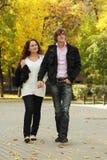 Coppie che camminano dalla sosta di autunno Immagine Stock