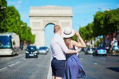 Coppie che camminano davanti all'arco trionfale a Parigi Immagine Stock Libera da Diritti