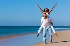 Coppie che camminano e che funzionano sulla spiaggia Fotografia Stock
