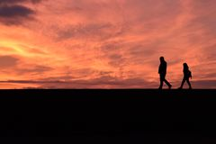 Coppie che camminano giù un tramonto molto arancio immagine stock libera da diritti
