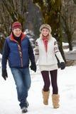 Coppie che camminano lungo la via dello Snowy nella stazione sciistica Immagini Stock
