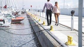 Coppie che camminano nel porto del porticciolo al giorno soleggiato video d archivio