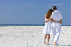 Coppie che camminano su una spiaggia vuota immagini stock libere da diritti
