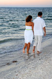 Coppie che camminano sulla spiaggia al tramonto fotografia stock
