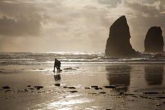 Coppie che camminano sulla spiaggia alla roccia del mucchio di fieno sulla costa dell'Oregon Fotografie Stock Libere da Diritti