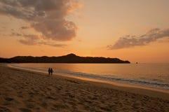 Coppie che camminano sulla spiaggia durante il tramonto. fotografia stock libera da diritti