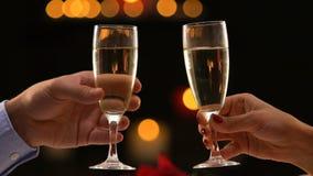 Coppie che celebrano nuovo anno che tiene i vetri con champagne, mani del primo piano archivi video