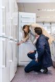 Coppie che comprano frigorifero domestico nell'ipermercato immagine stock libera da diritti