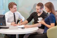 Coppie che comunicano con un rappresentante Immagine Stock