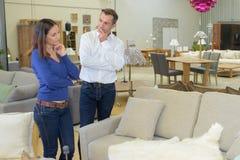 Coppie che contemplano nuovo sofà immagini stock