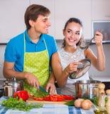 Coppie che cucinano le verdure alla cucina Fotografia Stock