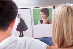 Coppie che esaminano album Fotografia Stock