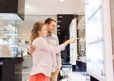 Coppie che esaminano alla finestra di compera la gioielleria Fotografia Stock