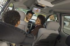 Coppie che esaminano bambino piccolo in automobile Immagine Stock
