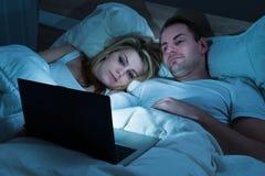 Coppie che esaminano computer portatile in camera da letto immagine stock