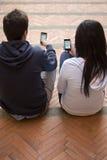 Coppie che esaminano i telefoni delle cellule Fotografia Stock Libera da Diritti