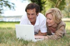 Coppie che esaminano il loro computer portatile Fotografia Stock