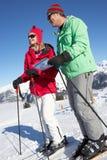 Coppie che esaminano programma mentre in montagne Immagine Stock