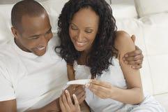 Coppie che esaminano test di gravidanza fotografia stock