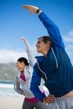 Coppie che eseguono allungando esercizio Immagine Stock Libera da Diritti