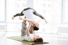 Coppie che fanno allenamento di flessibilità nello studio di yoga Immagini Stock Libere da Diritti