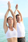 Coppie che fanno insieme yoga sulla spiaggia Fotografie Stock Libere da Diritti