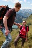 Coppie che fanno un'escursione in montagne Immagini Stock