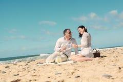 Coppie che fanno un picnic sulla spiaggia Fotografia Stock