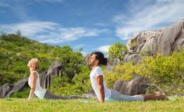 Coppie che fanno yoga cobra posare all'aperto Fotografia Stock Libera da Diritti