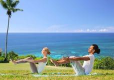 Coppie che fanno yoga mezzo barca posare all'aperto Fotografia Stock