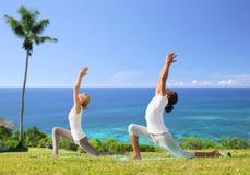 Coppie che fanno yoga nella posa bassa di affondo all'aperto Fotografia Stock Libera da Diritti