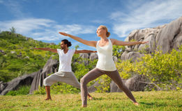 Coppie che fanno yoga nella posa del guerriero alla spiaggia Fotografia Stock Libera da Diritti