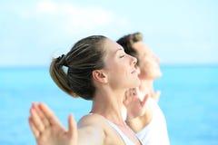 Coppie che fanno yoga sulla spiaggia Fotografia Stock
