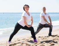 Coppie che fanno yoga sulla spiaggia fotografia stock libera da diritti