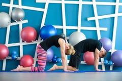 Coppie che fanno yoga in uno studio I giovani nella classe di yoga in gatto posano Concetto del gruppo di yoga fotografia stock libera da diritti