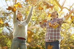 Coppie che gettano Autumn Leaves In The Air Fotografia Stock Libera da Diritti