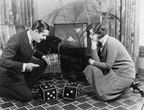 Coppie che giocano con i dadi enormi (tutte le persone rappresentate non sono vivente più lungo e nessuna proprietà esiste Garanz immagine stock