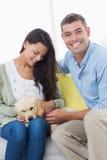 Coppie che giocano con il cucciolo sul sofà Fotografia Stock