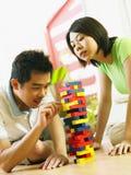 Coppie che giocano i giochi di legno della pila immagine stock libera da diritti