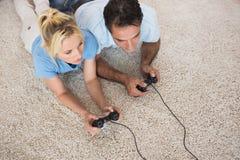 Coppie che giocano i video giochi sulla coperta di area a casa Immagine Stock