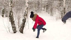Coppie che giocano le palle di neve nell'inverno in legno archivi video