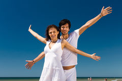 Coppie che godono della libertà sulla spiaggia Immagine Stock Libera da Diritti