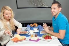 Coppie che godono di una prima colazione calorosa Fotografia Stock