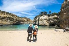 Coppie che guardano attraverso le rocce all'oceano Fotografia Stock Libera da Diritti