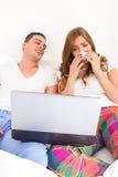 Coppie che guardano film drammatico a letto sul computer portatile Immagine Stock Libera da Diritti