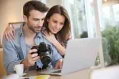 Coppie che guardano le foto prese su un computer portatile Fotografia Stock Libera da Diritti
